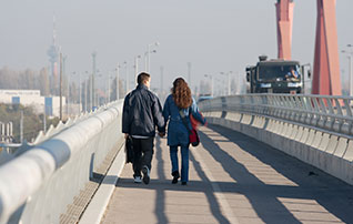 One man and one woman are walking on a bridge